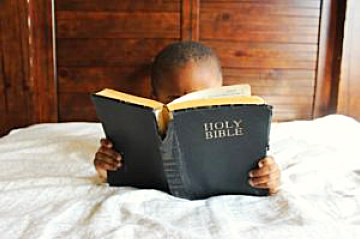 a little kid on a bed reading a bible
