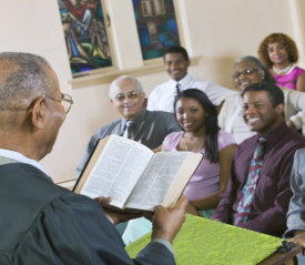 a pastor reading the bible to a group