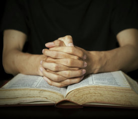 a man's hands holding together on top of a bible