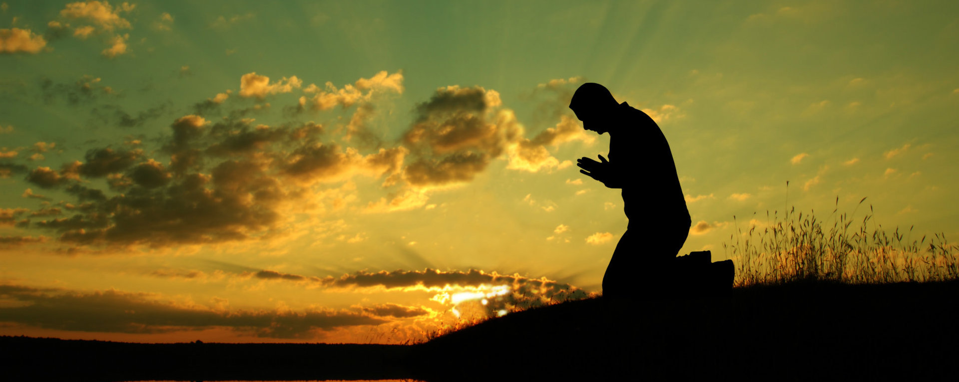 a silhouette of a man praying